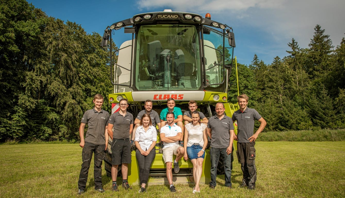 Team Pongruber Landtechnik vor einem CLAAS Mähdrescher