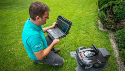 Servicetechniker mit Laptop beim Service eines Automowers